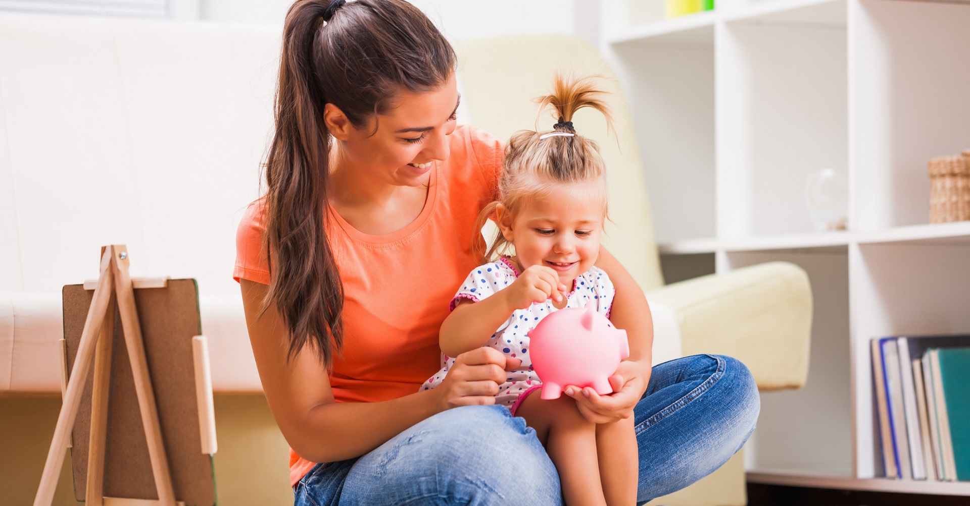 mother putting money in piggy bank with daughter