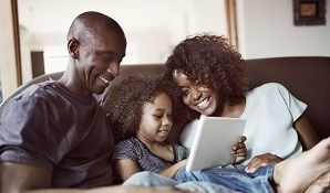 happy family sitting on couch looking at tablet