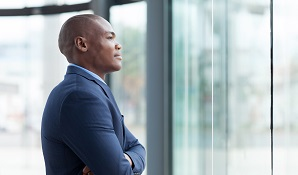 man in business suit staring outside window
