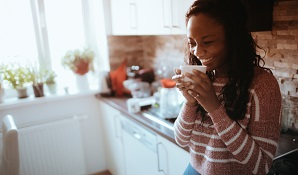 woman standing in kitchen drinking coffee