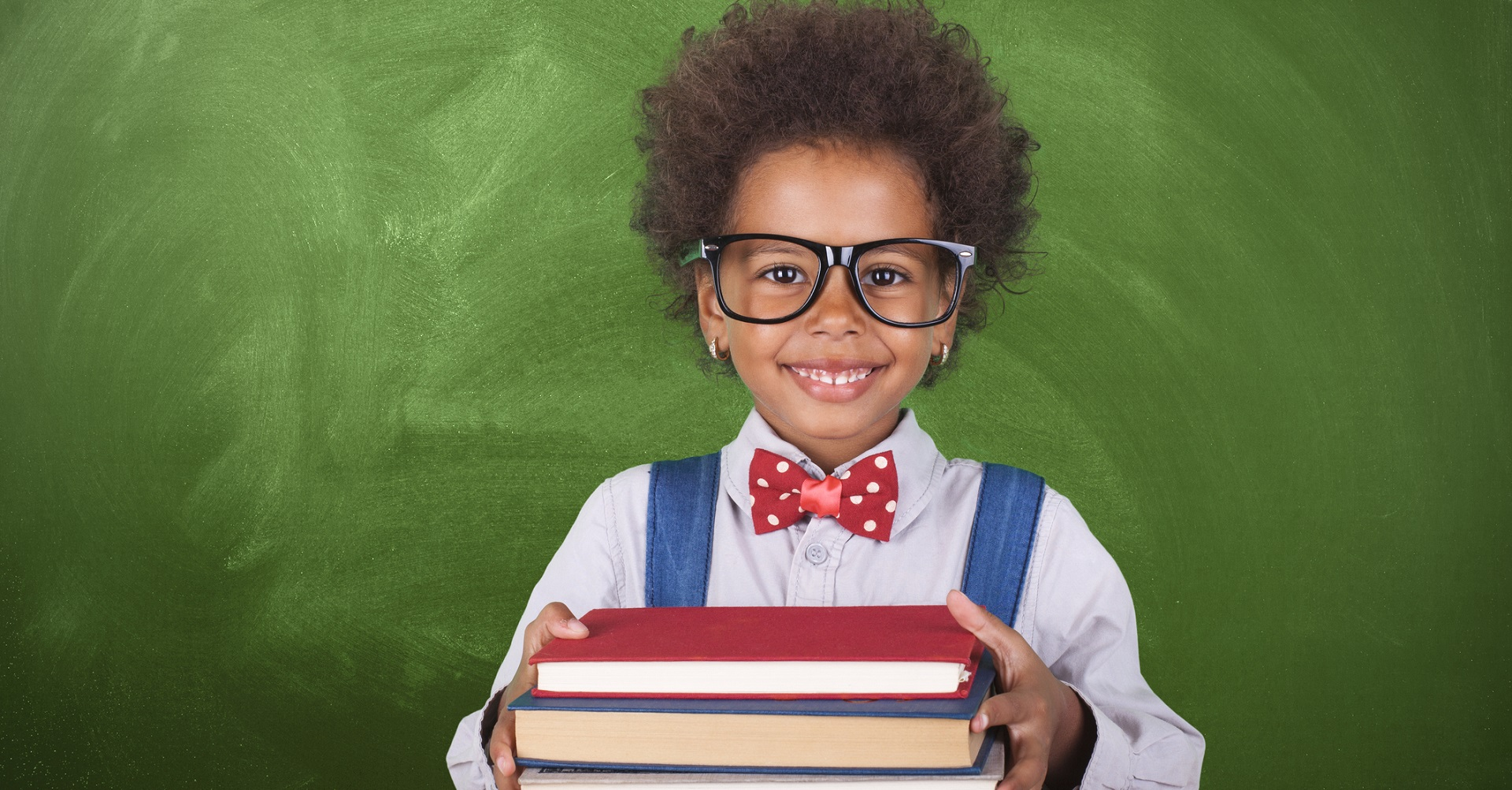 child with glasses holding school books