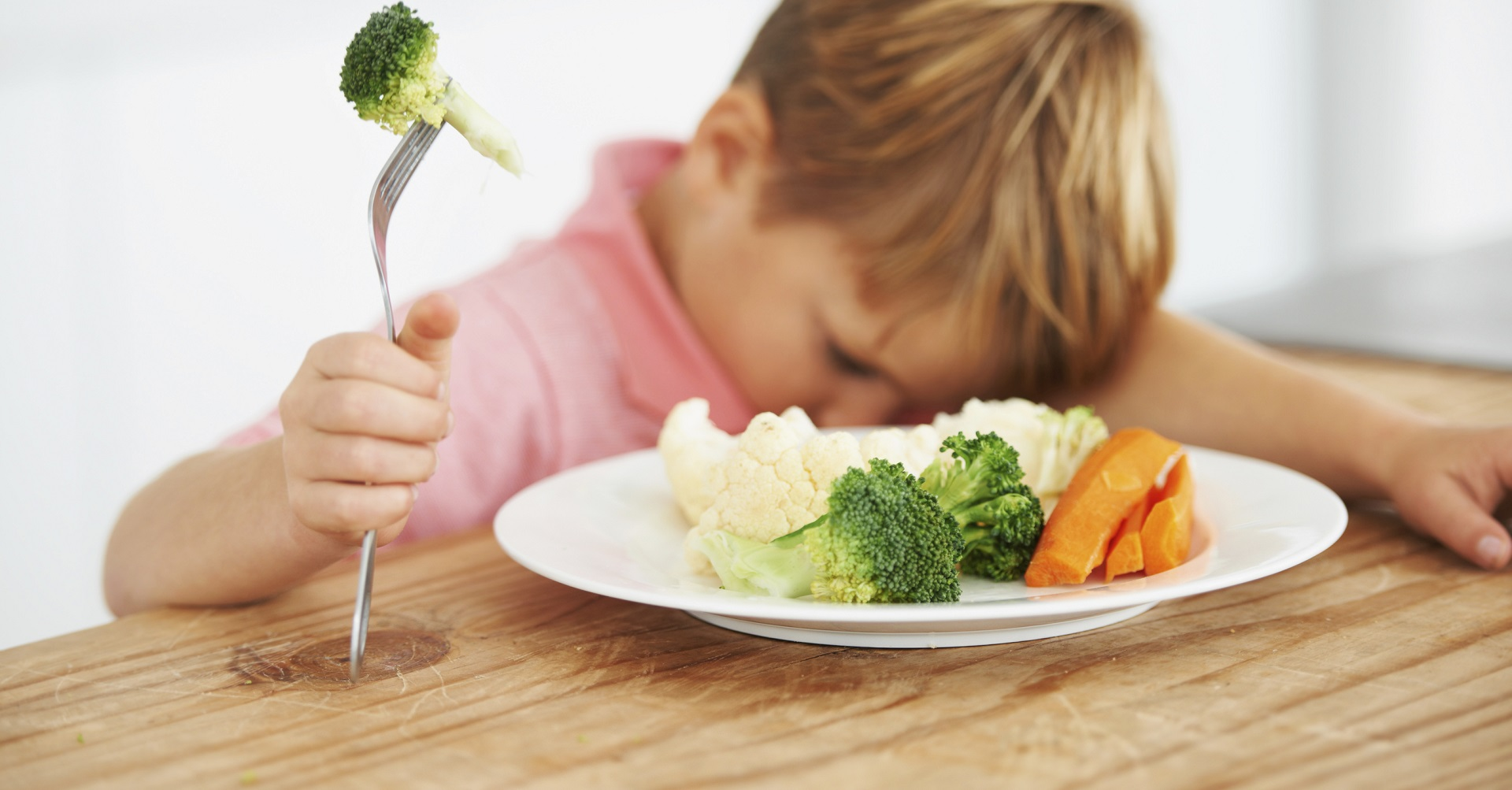 child sitting in front of plate of veggies