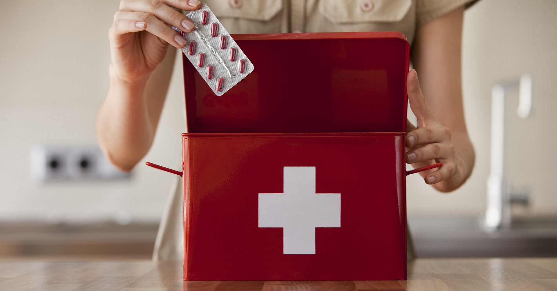 woman putting medicine into first aid kit
