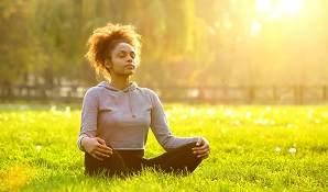 woman sitting on grass in the sun looking relaxed