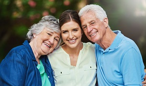Young lady hugging elderly parents