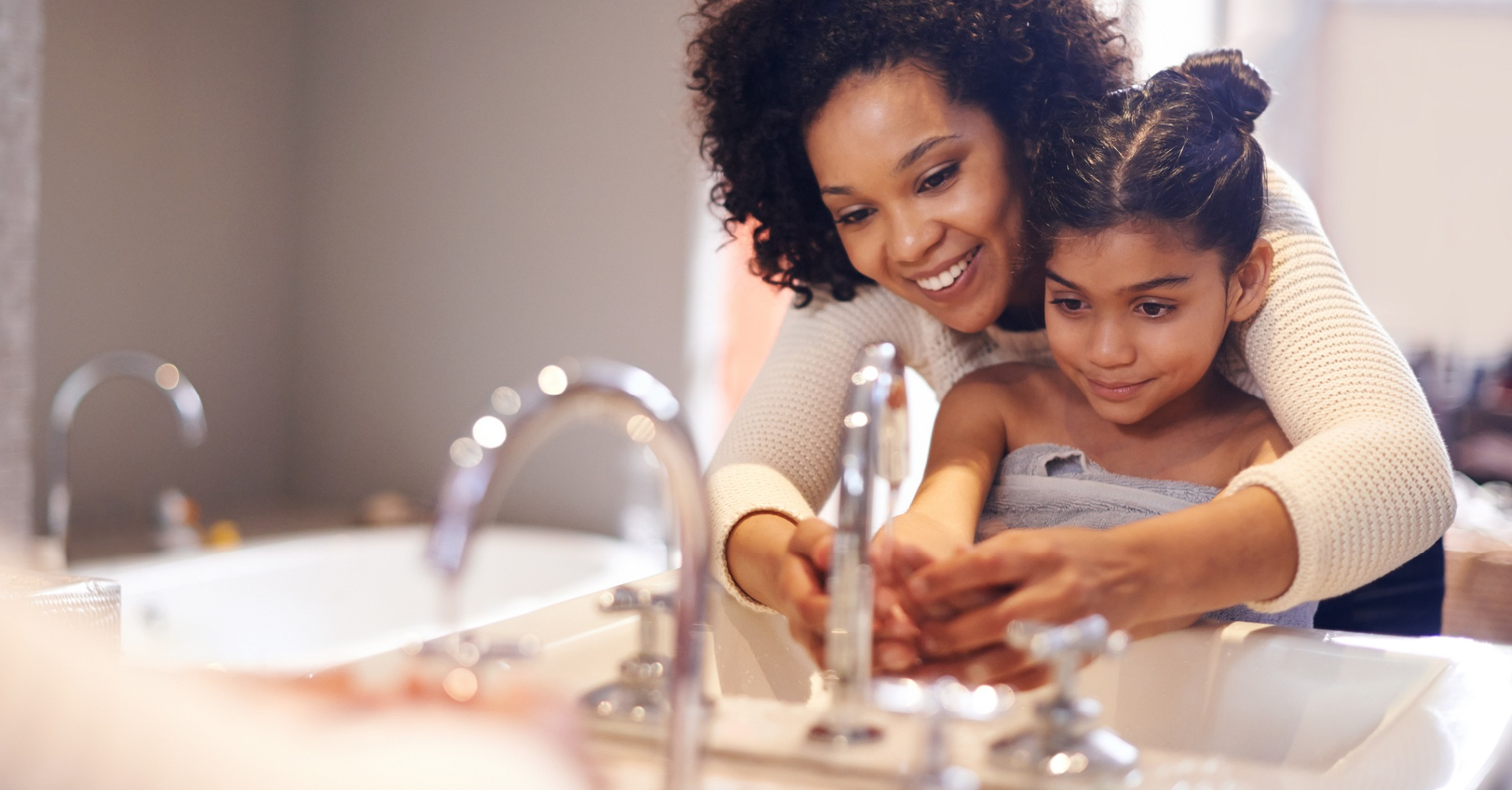 mother washing daughters hands in sink
